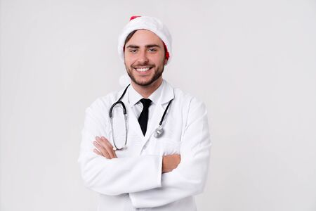 Young handsome doctor in white uniforme and Santa Claus hat standing in studio on white background loking in camer and teeth smile Portrait medical student Christmas New Year Holiday Medicine concept Stock Photo