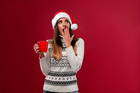 Close up portrait beautifiul caucasian woman in red Santa hat on red studio background. Christmas New Year holiday concept. Girl teeth smiling positive emotions with Red cup of coffee Lazy sleepyhead Foto de archivo