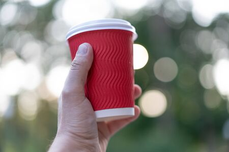 Red paper cup for drinks in hand on a background of nature. Cup coffee or tea from recyclable materials. Free space for text. Mock up.