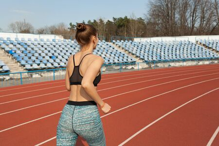 Young woman running during sunny morning on running track. Healthy lifestyle concept. Weight loss exercising