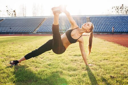 sport girl making yoga exercises outdoors. Young sport woman in a nature. Sport and fitness on open air. Stretching sitting on the grass 版權商用圖片