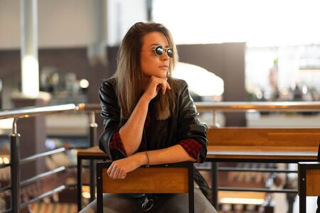 Beautiful hipster portrait caucasian woman cafe sunglasses leather black jacket trendy modern fashion lifestyle Pretty young girl Beautiful smiling Happy Girl sitting indoor cafe waitiing friends Stok Fotoğraf