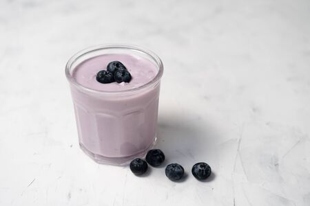 Tasty fresh blueberry yoghurt shake dessert in glass standing on white table background. Homemade berry smoothie. Healthy eating. Diet food yogurt Stok Fotoğraf