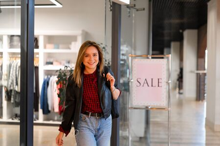Young beautiful girl goes out clothing store with purchases. Season sale happy young adult female. Modern girl in leather jacket and leans walking shopping mall on autumn spring sales