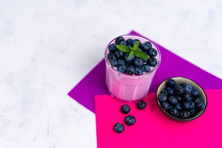 Tasty fresh blueberry yoghurt shake dessert in glass standing on white table purple napkin background. Homemade berry smoothie. Healthy eating. Diet food yogurt Stok Fotoğraf
