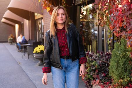 Beautiful young girl walking along the street next to shops Autumn season.  Happy people walk. Woman dressed Leather jacket and blue jeans outdoors. Free space for text. Modern female.