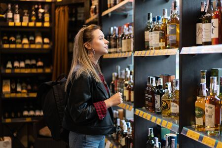 Ukraine. Kharkov Ocotber 2019 Young beautiful caucasian girl in a liquor store does not look at a shelf with bottles of whiskey. A modern woman wearing leather jacket and jeans buying alcohol