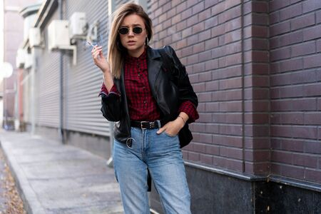 Beautiful young stylishly dressed Caucasian girl smokes cigarette on street Smoking bad habit Nicotine addiction Unhealthy lifestyle Modern woman leather jacket and jeans walking outdoor sunglasses