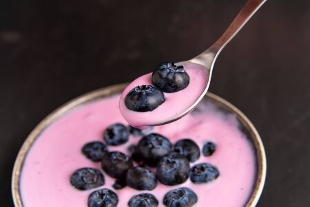 Tasty fresh blueberry yoghurt shake dessert in ceramic bowl standing on black table background. Homemade berry smoothie. Healthy eating. Diet food. Yogurt in spoon