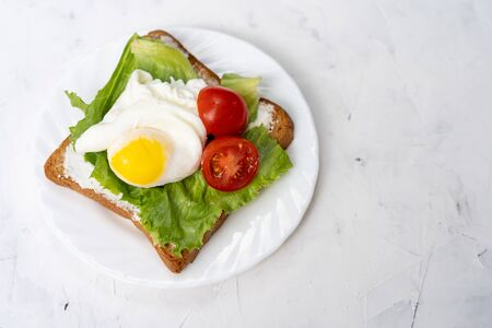 Sandwich with fried eggs salad and tomato on plate  white background with copy space