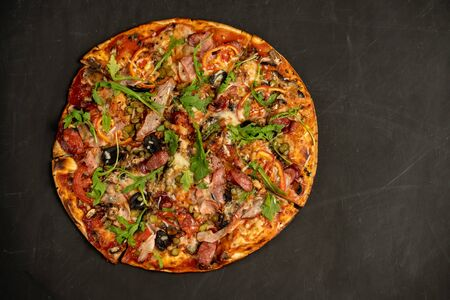 Appetizing pizza with smoked sausages bacon meat tomato cheese arugula on black dark background. With copy space for text