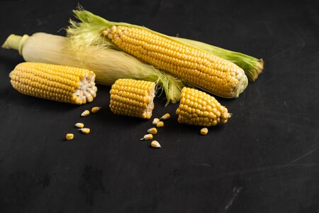 Corn cob with green leaves lies on table. black color background. Copy space for text.