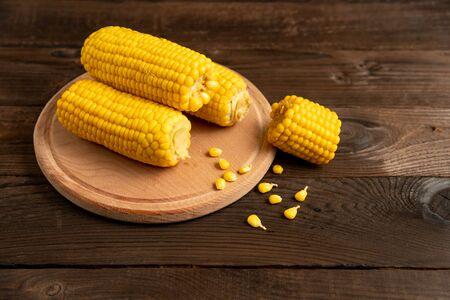 Corn cob with lies on round cutting board plate wooden table background. Copy space for text.