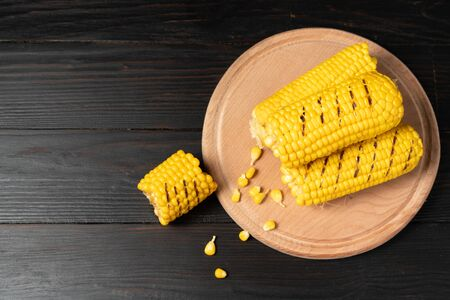 Grilled hot Corn cob lies on round cutting board plate wooden table background. Copy space for text.