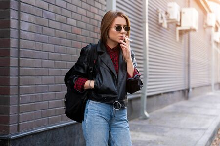 Young Adult caucasian woman jeans leather jacket backpack street modern style smokes cigarette Summer vacation concept Beauty fashion Young people concept Travel backpack concept bad habit