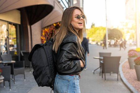 Young Adult caucasian woman jeans leather jacket  backpack street modern style laughs Summer vacation concept Beauty fashion Young people concept Travel backpack concept People hiking Happy female