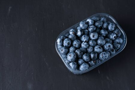 Tasty juicy raw blueberries in a plastic container on a black dark background. Packaging for berries in a supermarket on store shelves.