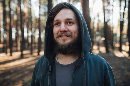 close up portrait of a bearded hipster tourist in gray hood man in the sunlight woods forest Concept Stok Fotoğraf