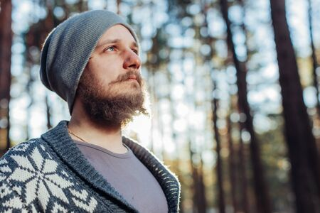 a young man with a beard walks in a pine forest. Portrait of a brutal bearded man Autumn forest tourism concept Stok Fotoğraf