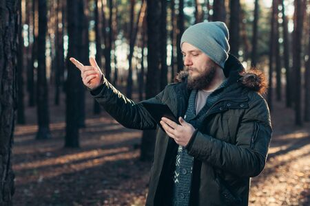 Portrait of adult man walking in the pine forest with digital tablet. Modern technology help navigate Stok Fotoğraf