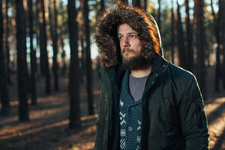 Portrait, close-up of young stylishly serious man with a beard dressed in rgreen winter jacket with a hood and fur on his head stands against the background of pine forest Stok Fotoğraf