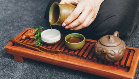 Traditional tea ceremony close up. Unrecognizable woman pours boiling water into ceramic cups for making delicious healthy aromatic tea