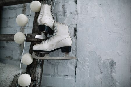 A pair of white leather sports skates hang on a cord on the wall. Good New Year spirit. Beautiful calm background Merry Christmas and Happy New Year Banque d'images