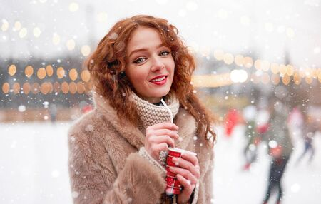 Young beautiful redhead girl freckles ice rink background Pretty woman curly hair portrait walking new year fair Modern cute female skate ice rink  chrismas holiday decorated street. Stock Photo