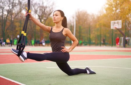 Girl athlete functional training sportground Mixed race young adult woman workout  suspension system Healthy lifestyle Stretching outdoors playground Make your body machine                             Imagens