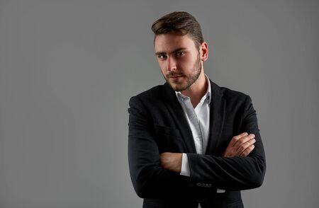 Nahaufnahme Porträt junger Mann Geschäftsmann. Kaukasischer Kerl Anzug Studio grauen Hintergrund. Moderne Geschäftsleute verschränkten die Arme vor der Brust Porträt eines charmanten erfolgreichen jungen Unternehmers Standard-Bild