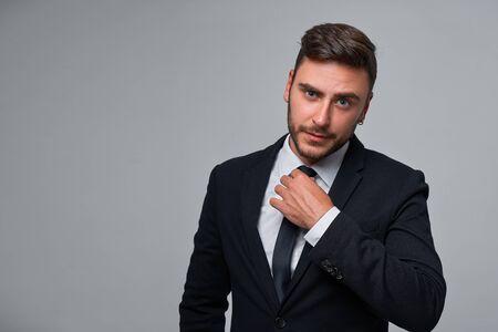 Close up portrait young man businessman. Caucasian guy business suit studio gray background. Modern business person straightens tie Portrait of charming successful young entrepreneur