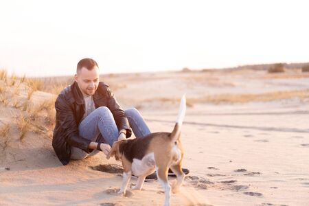 Young Caucasian man dressed black leather jacket and blue jeans sits on sandy beach next to his friend the dog Beagle breed. Handsome European guy walks with his dog in nature Love Friendship Fidelity