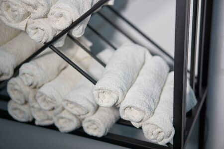 White clean towels rolled up on a roll are stored on shelves in a beauty salon in a barbershop spa. Close up towel storage