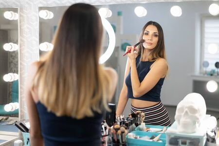Portrait of pretty female beautician standing posing at workplace in hair and beauty salon with big mirror on the background