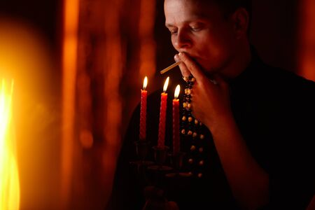 Young adult caucasian catholic priest on dark red background Handsome pastor father pray indoors in dark authentic church Smoking cigarette, smoker with bad habit. Addiction