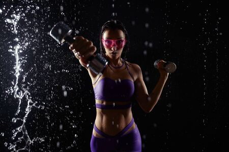 Beautiful young girl in purple sportswear poses with dumbbells in aqua studio. Drops of water spread about her fitness body. The perfect figure on the background of water splashes. Banque d'images