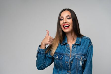 Beautiful caucasian girl denim jacket posing in studio on white background Cute brunette Denim fashion red lips make up Young adult woman standing indoors surprised admired Shows thumbs up sign gesture
