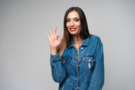 Beautiful caucasian girl denim jacket posing in studio on white background Cute brunette Denim fashion red lips make up Young adult woman standing indoors surprised admired Shows ok sign gesture