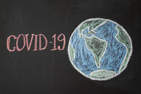 Planet Earth in danger Outbreak Warning. written white chalk on blackboard in connection with epidemic of coronavirus worldwide. Covid 19 pandemic Text on black background