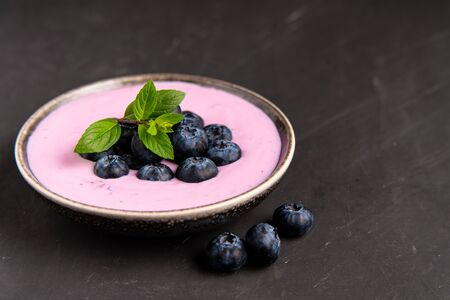 Tasty fresh blueberry yoghurt shake dessert in ceramic bowl standing on black table background. Homemade berry smoothie. Healthy eating. Diet food. yogurt