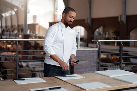 Handsome young chef African ethnicity lays knives on table in front of a culinary master class. Afro man in chef uniform getting ready for cooking classes. Stock Photo