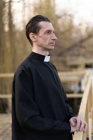 Portrait of handsome catholic priest or pastor with collar Standing outdoors Stock Photo