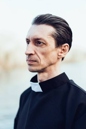 Portrait of handsome catholic priest or pastor with collar Standing outdoors Stok Fotoğraf