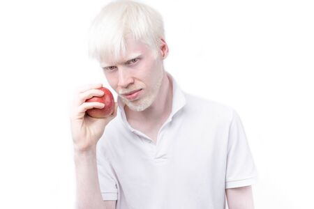 Happy albino man white skin hair studio dressed t-shirt isolated white background. abnormal deviations. unusual appearance. skin abnormality Beautiful people with special appearance. Eat red apple Banque d'images