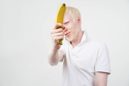 Happy albino man white skin hair studio dressed t-shirt isolated white background. abnormal deviations. unusual appearance. skin abnormality Beautiful people with special appearance. Eat banana