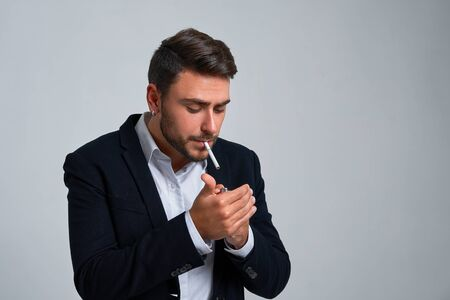 Close up portrait young man businessman Caucasian guy business suit studio gray background. Modern business person stylish haircut smokes a cigarette Portrait of charming successful young entrepreneur