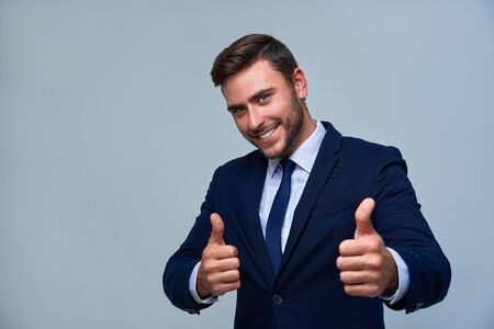 Portrait young smiling businessman. Caucasian guy business suit tie studio gray background. Modern business person Showing thumbs up sign. Portrait of charming successful happy entrepreneur Zdjęcie Seryjne