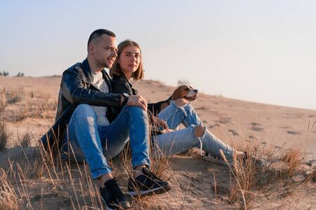 Young beautiful caucasian couple wearing leather jacket and jeans walks desert sand with Beagle dog best friend. Family with dog without children resting in nature. positive emotions happy people
