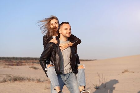 Happy and cute adorable adult couple leather jacket and jeans man with woman girlfriend on piggy back, have fun play, laugh,smile and jump on sunset at desert crazy in love, emotions and relationship