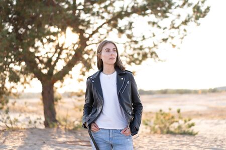 Young beautiful caucasian woman dressed leather jacket and jeans stands on the beach The rays of the sun break through the foliage of a tree background European girl in casual clothes walking outdoor